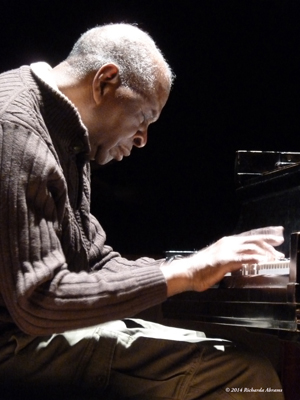 A photo of the right profile of Muhal Richard Abrams playing the piano copyright 2014 Richarda Abrams